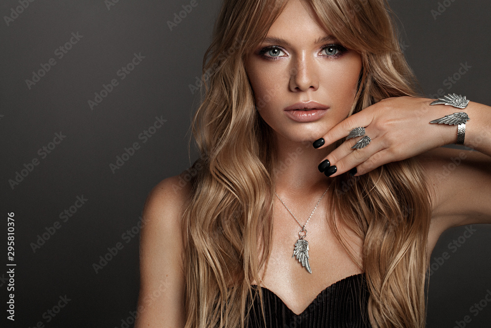Fototapeta Beautiful woman with set jewelry . Woman in a necklace with a ring and a bracelet wings shape. Studio with Gray background with copy space. Beauty and accessories.