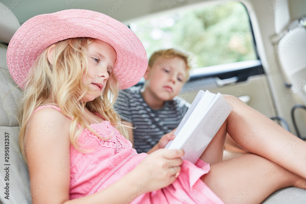 Fototapety, obrazy: Girl in the car reads a thrilling book