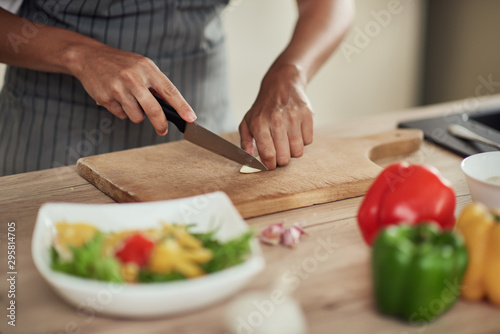 Fotomural  Close up of mixed race woman in apron standing in domestic kitchen and cutting garlic