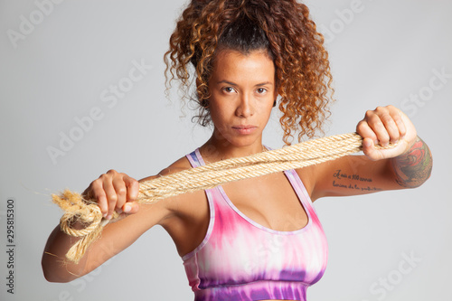 Photo Chica joven y bella, deportista con una cuerda en sus manos, pelo rizado y de pi