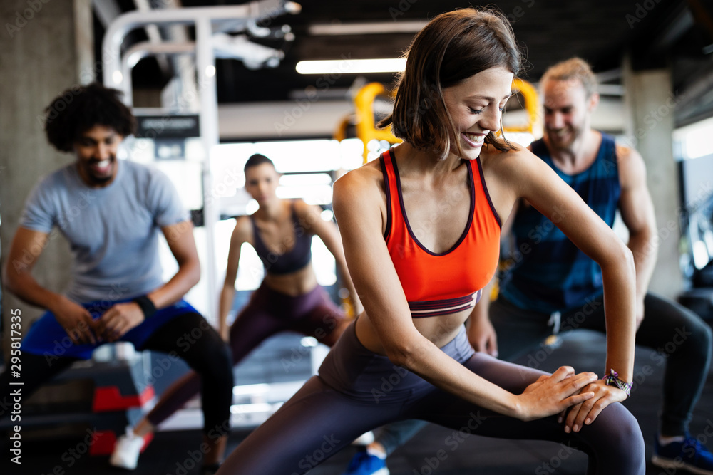 Fototapety, obrazy: Happy fit friends exercising, working out in gym to stay healthy together