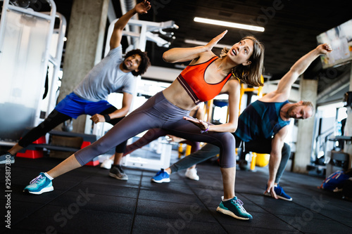 Healthy young people doing exercises at fitness studio. - 295817380