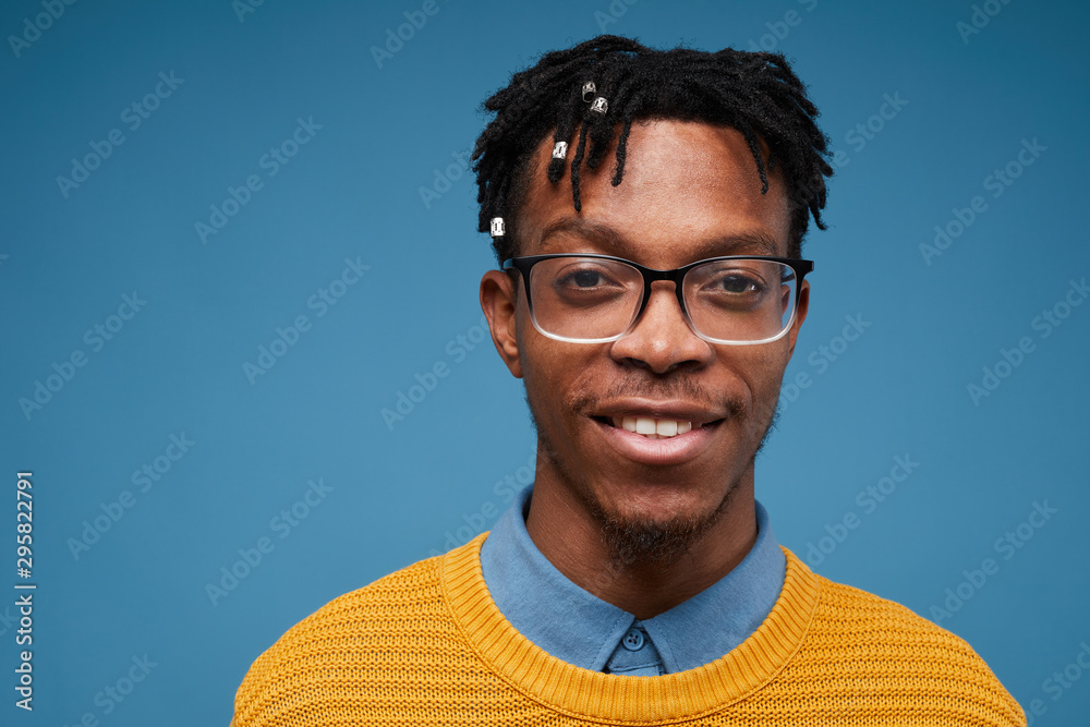 Fototapeta Head and shoulders portrait of contemporary African-American man smiling at camera while wearing bright knit sweater and posing against blue background, copy space