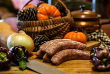 Selective Focus Still Life Of Preparation Of German Bratwurst Purple Peppers And Onions On Wooden Cutting Board With A Large Knife, With Blurred Basket Of Pumpkins And Pine Cones In Background