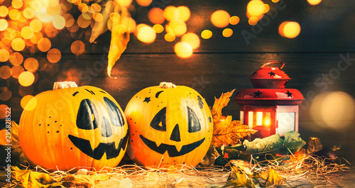 Poster Halloween festive composition with smiling pumpkins guards with lights, lantern, straw and fallen leaves on dark wooden background, rustic style, selective focus
