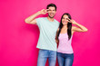 Leinwandbild Motiv Photo of funny couple guy and lady raising hands showing v-sign symbols near eyes wear casual clothes isolated bright pink color background