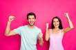 Leinwandbild Motiv Photo of crazy couple guy and lady celebrating first startup big incoming raising fists wear casual clothes isolated vibrant pink color background