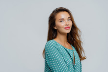 Profile Shot Of Pretty Pleased Woman Wears Makeup, Rosy Lipstick, Dressed In Polka Dot Blouse, Has Healthy Skin, Poses Against White Background With Blank Space For Your Advert Or Promotion.
