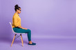 Leinwanddruck Bild - Full length profile photo of pretty dark skin lady on chair look empty space listen employer question interview wear specs yellow shirt trousers isolated purple color background