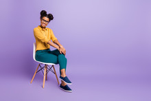 Full Length Photo Of Amazing Dark Skin Lady Sitting On Chair Looking Positive Listen Employer Question Wear Specs Yellow Shirt Trousers Isolated Purple Color Background