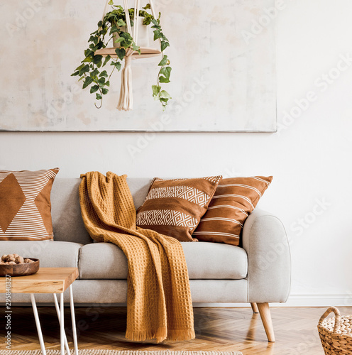 Modern boho interior of living room at cozy apartment with gray sofa, honey yellow pillows and plaid, plants, paintings, rattan basket and design personal accessories Wallpaper Mural