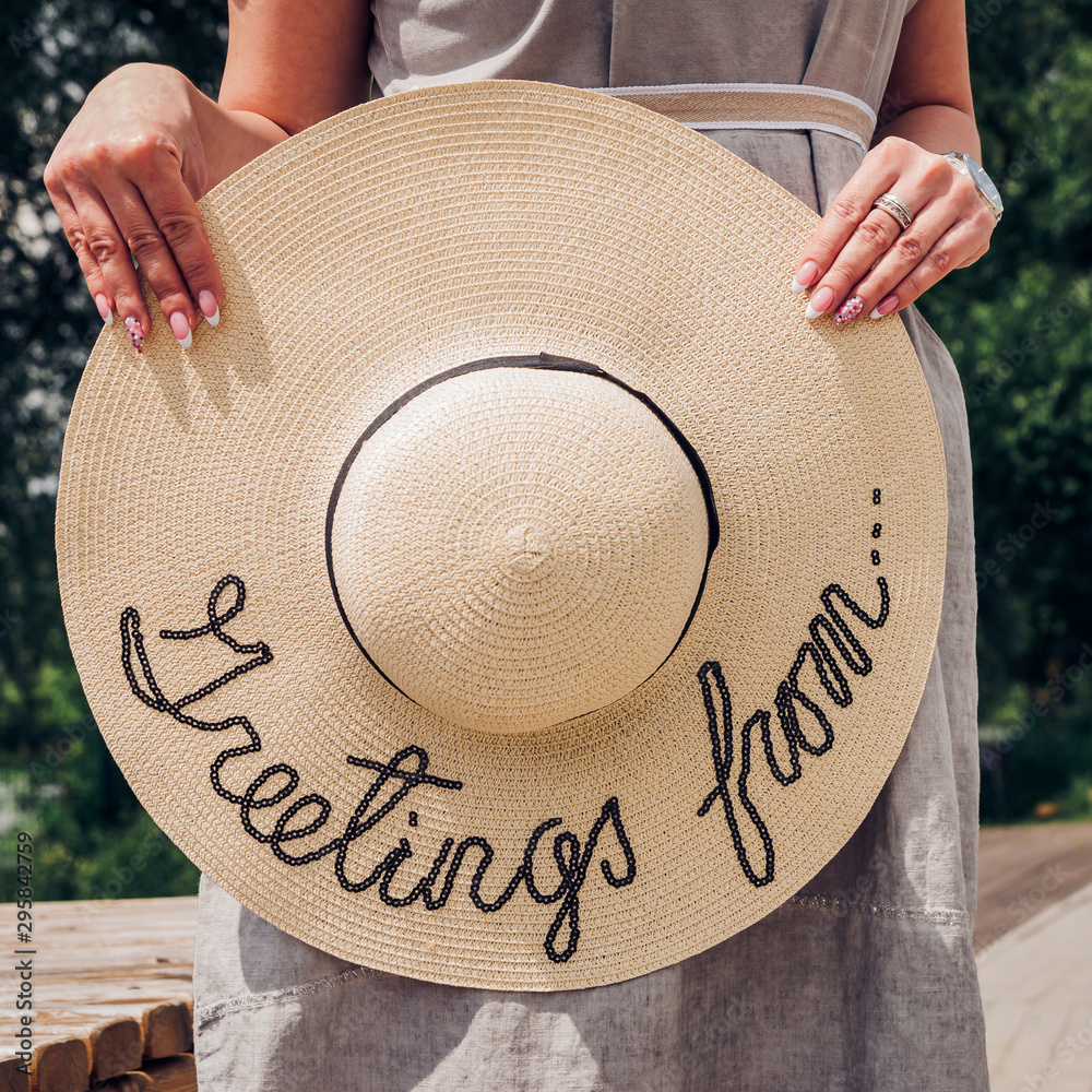 Fototapety, obrazy: A woman holds in her hands a large round straw hat on the street.