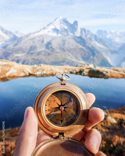 Man with compass in hand in high mountains near clear lake. Travel concept. Landscape photography