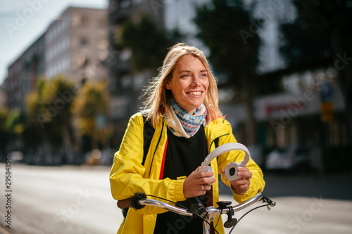 Young woman on bicycle putting headphones on - 295848562