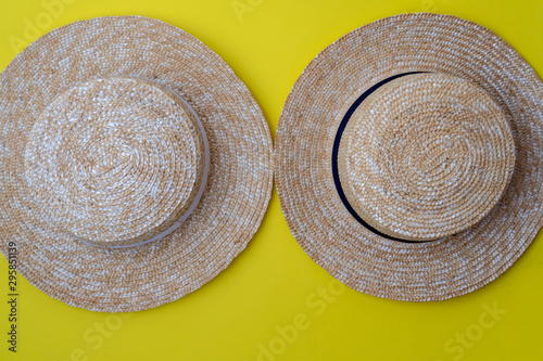 Modern stylish boater straw hats on a yellow background Wallpaper Mural