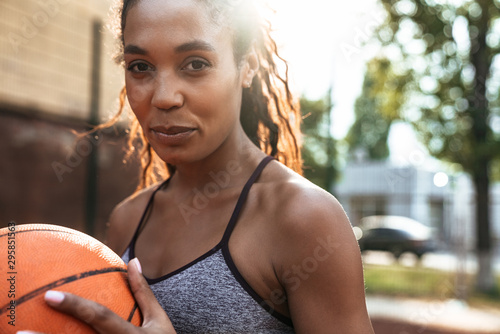 Attractive young african sportswoman playing basketball Fototapete