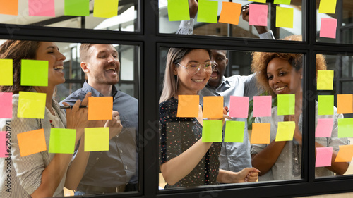 Fotografía  Behind glass wall standing businesspeople celebrating successful accomplishment