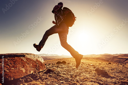 Fototapeta Man with backpack jumps to big rock