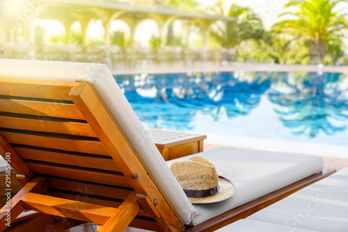 Fotografia, Obraz Lounger with sun hat and swimming pool in luxury resort