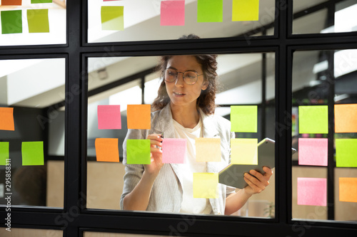 Fotomural  Businesswoman creates priority to-do list on sticky notes