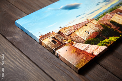 Obraz Canvas photo print on brown wooden background. Side view of colorful photography with gallery wrap. Photo printed on glossy canvas closeup - fototapety do salonu
