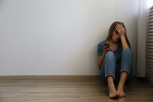 Portrait Of Beautiful Young Woman With Depressed Facial Expression Sitting In The Corner Holding Her Phone. Cyber Bullying Victim Concept. Sad Female On The Floor Of Her Room. Background, Copy Space.
