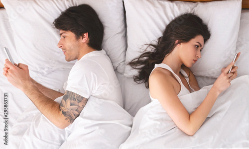 Poster Individuel Millennial couple in quarrel, lying in bed back to back, using cellphones