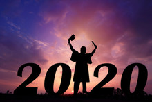 Happy New Year Silhouette Sunset Background.He Is Wearing Graduate's Dress And Standing Between Number 20 And 20.He Raised Hand.graduation,year,success,2020, Photo Concept Silhouette And New Year.