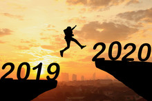 Happy New Year Silhouette Sunset Background. A Man Jumping Over Cliff And Jump Between 2019 And 2020 Years. Photo Silhouette And New Year  Concept Idea.