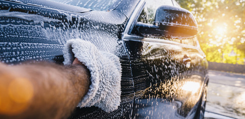 Man worker washing black SUV with sponge on a car wash.