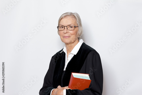 Female jurisdiction concept: mature german woman in a black judge's gown holding a legislative text book Fototapeta