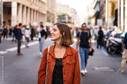 plakat Blonde girl in the middle of the street with happy expression walking around with an orange jacket and a bag and looking to the side.