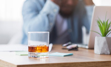Desperate Black Businessman Suffering From Bankruptcy, Drinking Alcohol At Workplace.