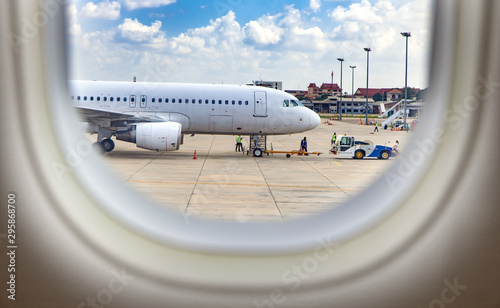View trough window of aircraft at Airplane standing on International Airport Wallpaper Mural