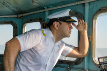Captain Standing In The Wheelhouse And Looking To Ahead. A Sailor In The White Uniform Looking To Sea From Control Room - Navigation Bridge.