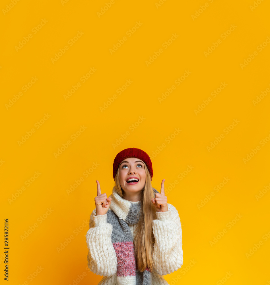 Fototapety, obrazy: Amazed girl in red hat pointing up at copy space