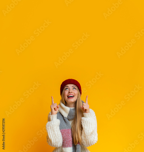 Amazed girl in red hat pointing up at copy space Fototapet