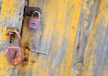 Closeup Of Old Lock On Yellow Weathered Wooden Door