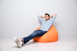 Leinwanddruck Bild - Turned full length body size photo of cheerful confident relaxing man sitting in chair thinking guessing smiling toothily having rest fun isolated over grey color background