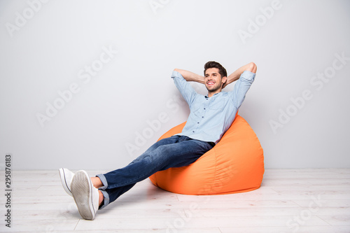Obraz Turned full length body size photo of cheerful confident relaxing man sitting in chair thinking guessing smiling toothily having rest fun isolated over grey color background - fototapety do salonu