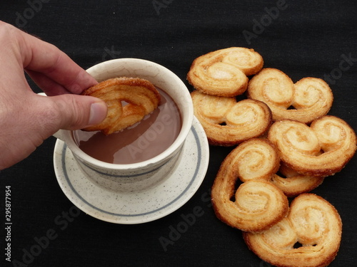 Fotografia, Obraz Hand wetting a heart-shaped puff pastry (palmeritas) in a white cup of chocolate with a black background