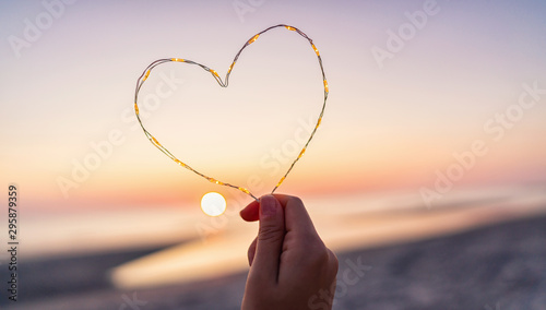 Fotobehang Strand womand holding Heart shape made of led lights at the beach on sunset