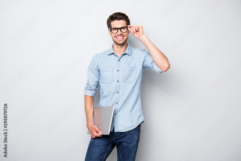 Fototapeta Photo of cheerful handsome attractive clever man smiling toothily holding laptop with hands showing his intelligence with style isolated over grey color background
