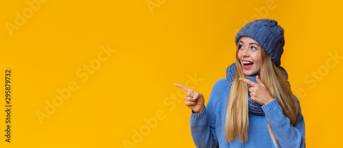 Fototapeta Excited girl pointing at free space over yellow background obraz