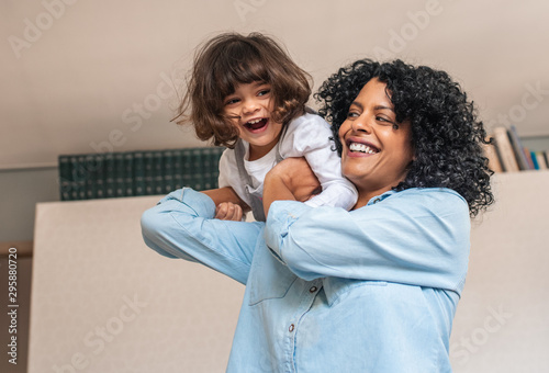 Foto  Laughing mom and cute little daughter playing at home