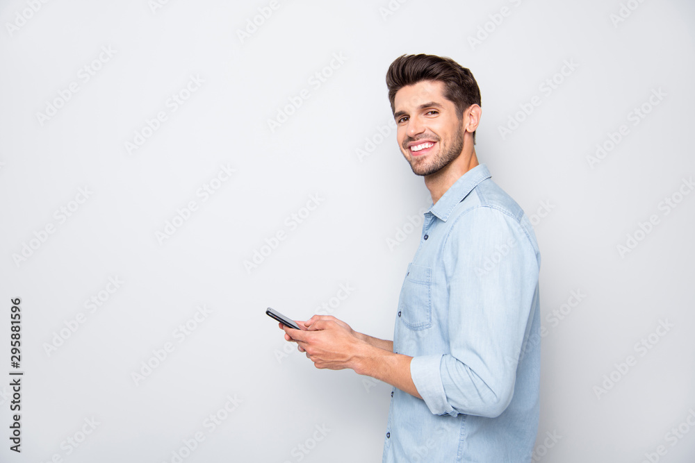 Fototapeta Profile side photo of positive cheerful man using holding his mobile phone have online conversation with friends on social media at copyspace wear stylish outfit isolated over grey color background