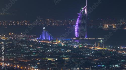 Fotografía  Aerial view of Dubai city skyline at night with illuminated burj al arab hotel timelapse