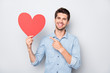 Portrait of charming man with positive emotions expression hold hand red big paper card heart present his gift for 14-february to girlfriend wear casual style clothes isolated grey color background