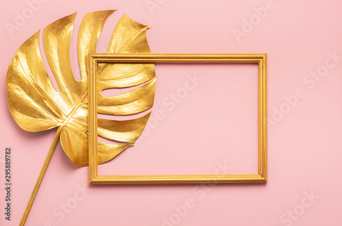 Fototapeta The square frame and leaf of tropical monstera plant are painted in gold color pink background. Art concept minimalism. obraz