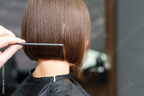 Obraz Close up of a hairdresser combs the short brown hair of her client in beauty salon background. Professional hair care concept. - fototapety do salonu